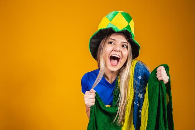 Блондинка бразильский фанат празднует на желтом фоне с флагом бразилии