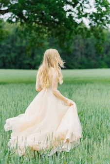 Blonde bride in beige wedding dress runs across the field forward on the grass