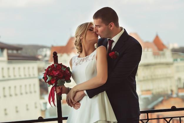 Blonde bride and brunette groom walking near the terrace