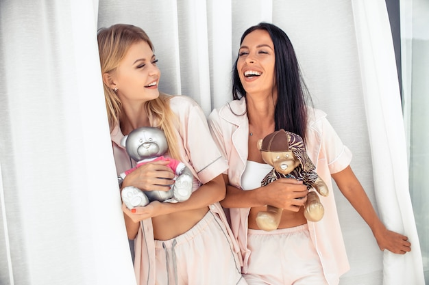 Blonde and brunette laughing in pajamas with toy bears standing on the balcony