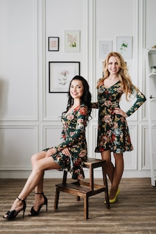 Blonde and brunette in short green dresses with patterns. two beautiful girls in a white studio.