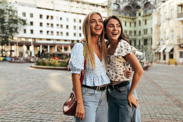 Blonde and brunette women in stylish outfits look away in good mood