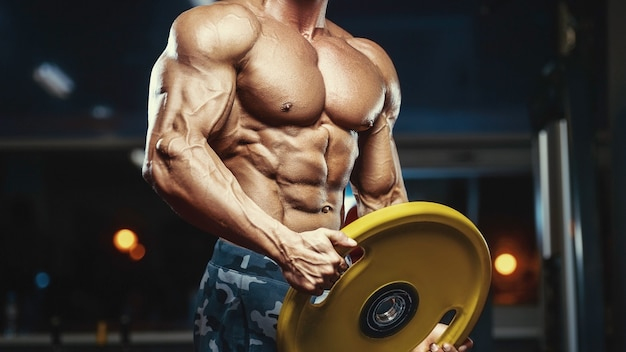 Blonde brutal strong bodybuilder athletic fitness man pumping up abs muscles workout bodybuilding concept