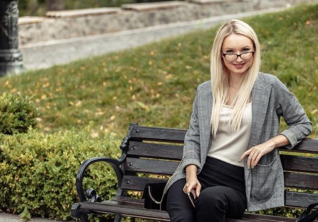 公園のベンチに座っている金髪のビジネスレディ