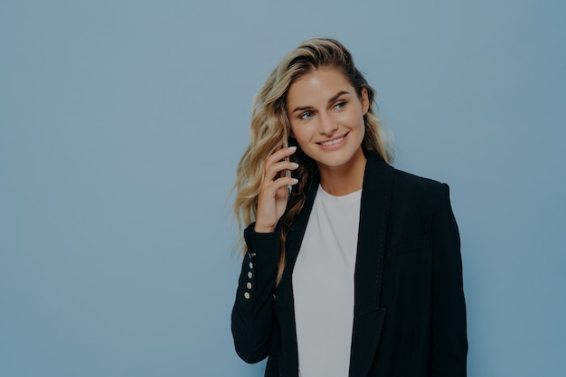 Blonde business woman in black jacket talking on mobile phone with family, happy to hear good news, listening and looking sideways while standing isolated on blue background. communication concept
