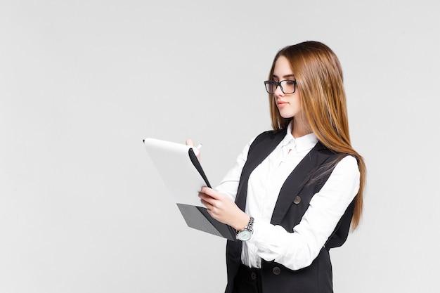 金髪のビジネス女性は白い壁に分離された板紙を保持します。