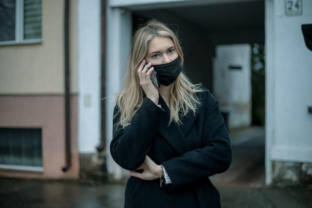 검은 코트와 건물의 아치를 배경으로 스마트 폰을 사용하여 그녀의 얼굴에 마스크에 금발 비즈니스 여자.