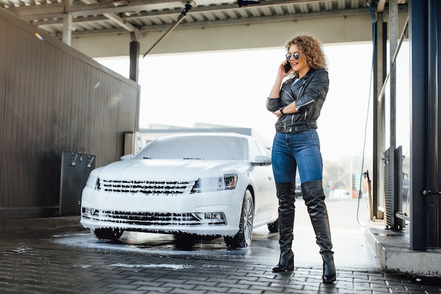 Blonde business woman speak by phone near her car on wash service car