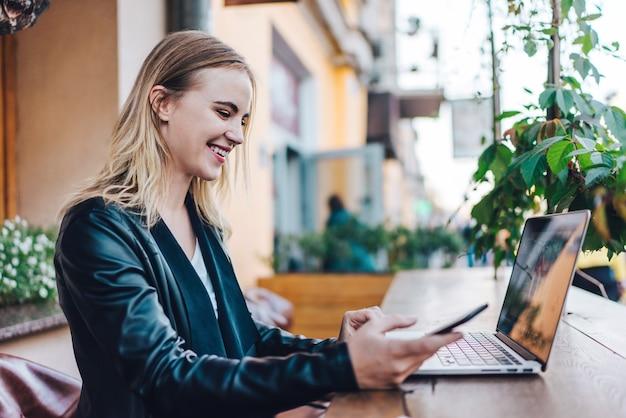 携帯電話とラップトップを使用して彼女の新しいプロジェクトに取り組んでいるストリートカフェで彼女の昼食時間を過ごす金髪のビジネスウーマン