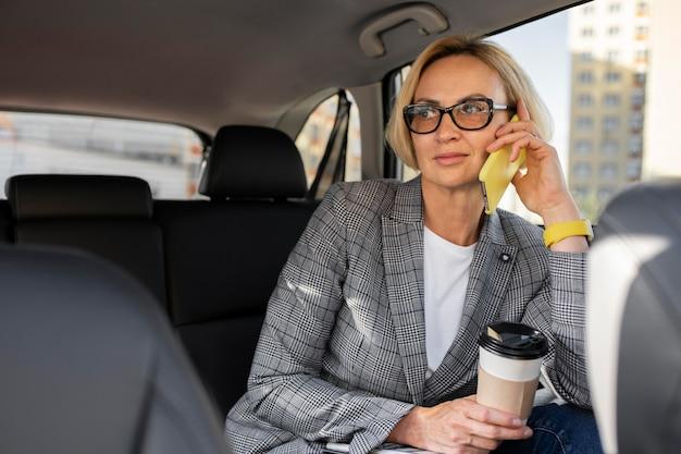 Блондинка бизнес женщина разговаривает по телефону в ее машине
