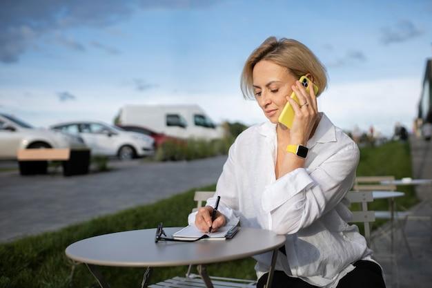 彼女の電話で話している金髪のビジネス女性