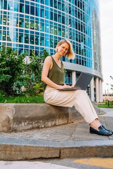 Blonde business woman wearing glasses sit with laptop among the skyscrapers and work.