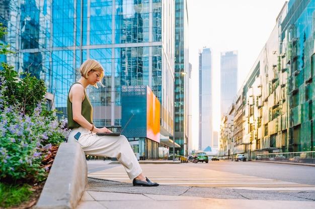 眼鏡をかけている金髪のビジネス女性は、高層ビルの中でラップトップと一緒に座って仕事をしています。