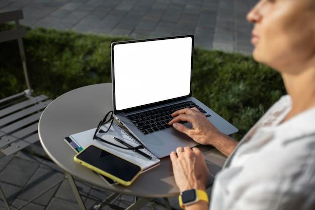 Donna d'affari bionda che lavora al suo computer portatile all'aperto