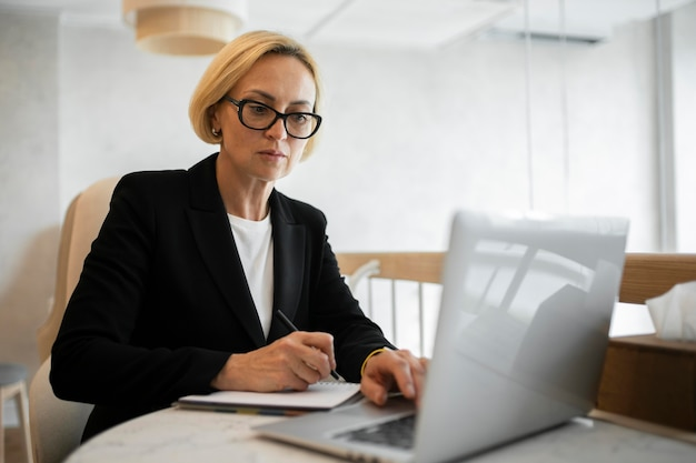 Blonde business woman working on her laptop