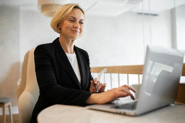 Donna d'affari bionda che lavora al suo computer portatile