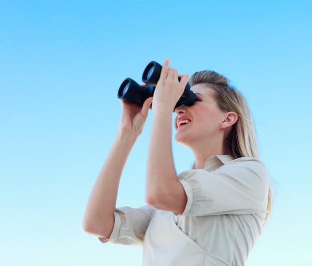 Blonde businesswoman looking through binoculars