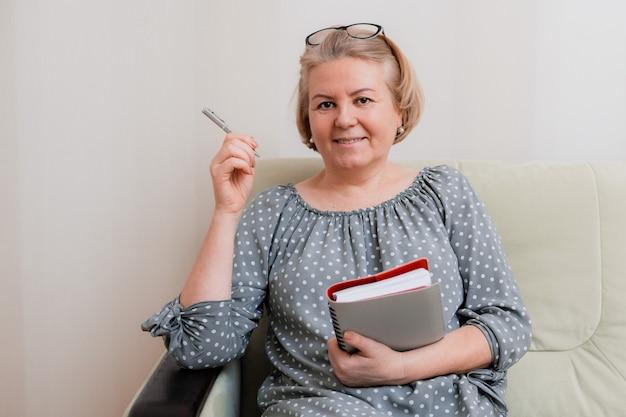 Блондинка деловая женщина, улыбающаяся и пожилая, в очках, читает и просматривает с помощью ежедневника и шариковой ручки. портрет красивой ухоженной пенсионерки 50-60 лет в номере.