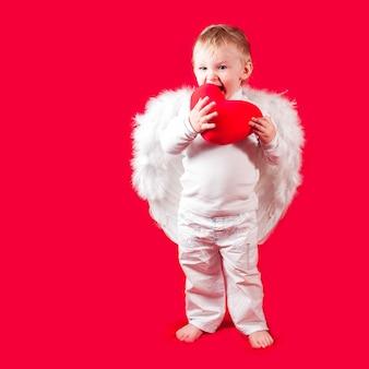 Blonde caucasian boy - valentine - with yummy heart on red background. cute valentine concept