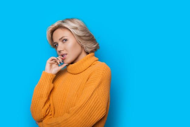 唇に触れて、空きスペースのある青い壁にポーズをとって黄色のセーターで金髪の白人の魅力的な女性