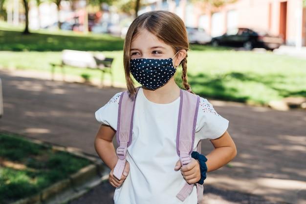 Covid19コロナウイルスのパンデミックのために彼女の顔にマスクを付けて年の初めに学校に行く金髪の白人の女の子