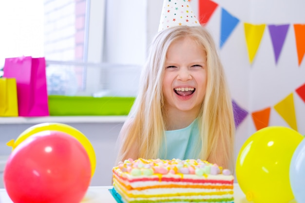 Blonde caucasian girl laughing at camera near birthday rainbow cake. festive colorful background with balloons