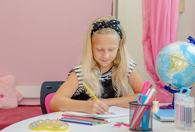 Белокурая кавказская девушка учится дома.