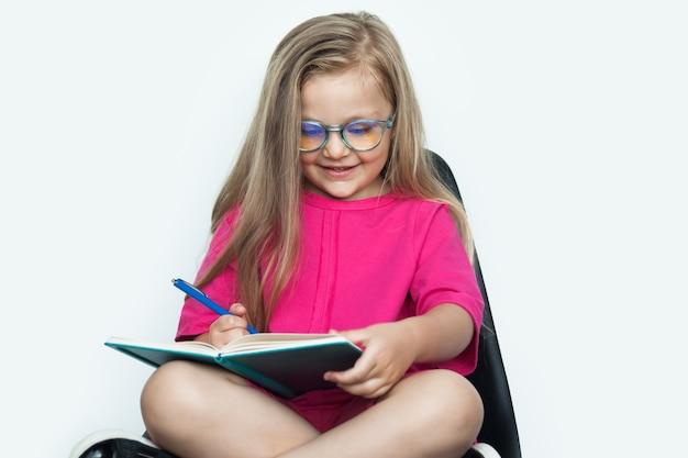 白いスタジオで赤いシャツを着ている間、本に何かを書いている眼鏡をかけた金髪の白人の女の子