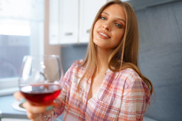 彼女の台所に立っている赤ワインのガラスと金髪の白人の幸せな女性