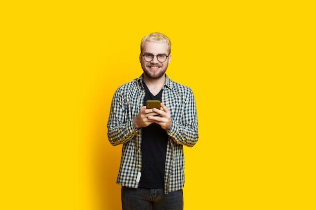 金髪の白人男性が黄色い壁に眼鏡をかけている間、電話を使用して誰かとチャットしています