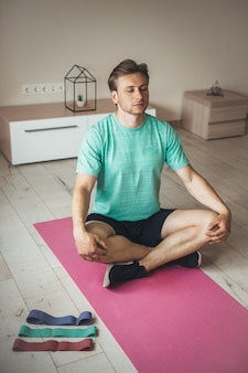 Blonde caucasian man practice yoga at home on a pink carpet on the floor with some elastic bands near