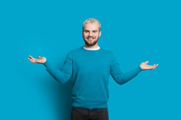수염을 가진 금발 백인 남자는 파란색 벽에 포즈를 취하는 동안 균형을 몸짓으로