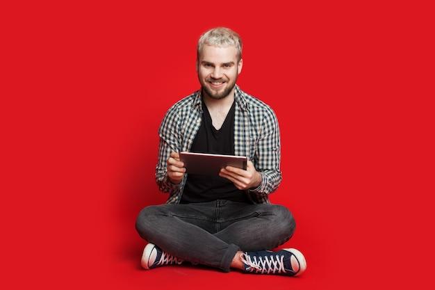 Блондинка с бородой сидит на полу с помощью планшета и смотрит в камеру на красном фоне