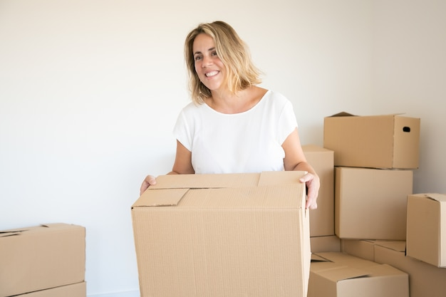 Blonde caucasian woman carrying carton box in new house or apartment