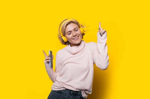 音楽を聴きながら黄色の壁で踊る金髪の白人女性
