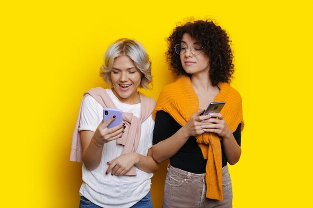 금발의 백인 여자는 전화를 들고 노란색 벽에 그녀의 곱슬 머리 친구 근처 포즈