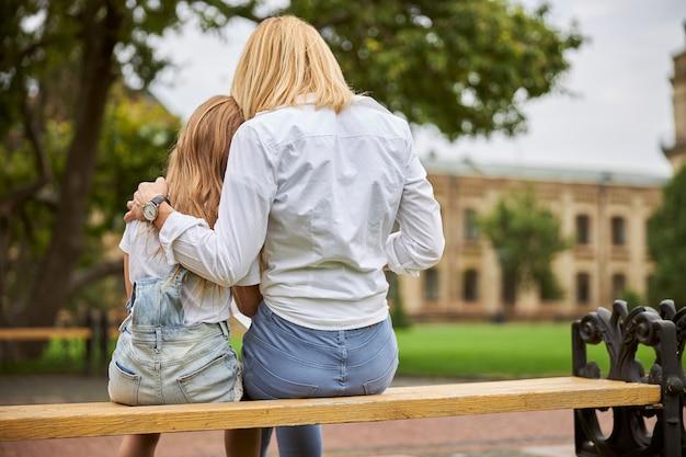 도시 공원에서 함께 쉬고있는 동안 그녀의 어린 딸을 포옹 금발 백인 여자