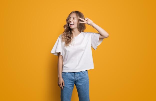 白いシャツとジーンズの金髪の白人女性が黄色のスタジオの壁で笑い、指で平和を身振りで示す