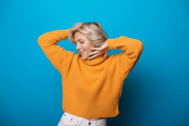Белокурая кавказская женщина в желтом вязаном свитере показывает удовольствие на синей стене студии