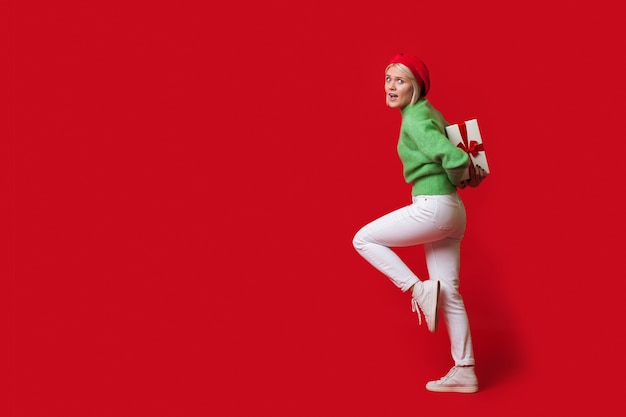 Blonde caucasian woman is carrying a present box on her back wearing a hat and looking at camera on a red wall with free space