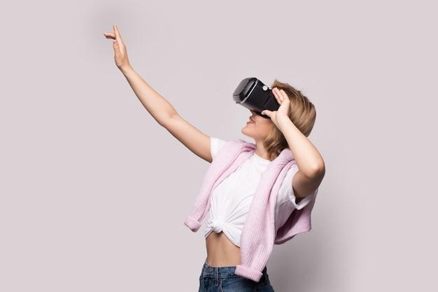 Белокурая кавказская женщина трогает что-то во время опыта виртуальной реальности со специальной гарнитурой на белой стене студии