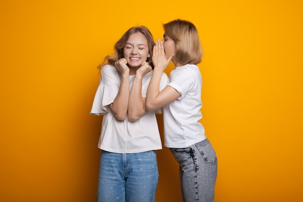 Blonde caucasian woman is whispering something to her friend posing in casual clothes on a yellow studio wall