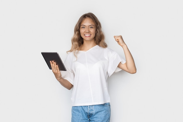 Blonde caucasian woman smiling toothily on a white  wall gesturing the power sign and holding a tablet