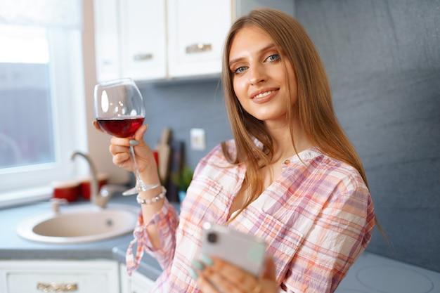 彼女のキッチンに立っている赤ワインのガラスを持つ金髪の白人女性