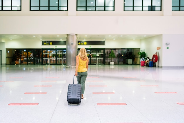 A blonde caucasian woman in a yellow shirt walking in an airport with her luggage