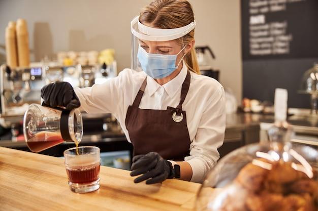 커피 바에서 일하는 보호용 약 마스크를 쓴 금발의 매력적인 여성