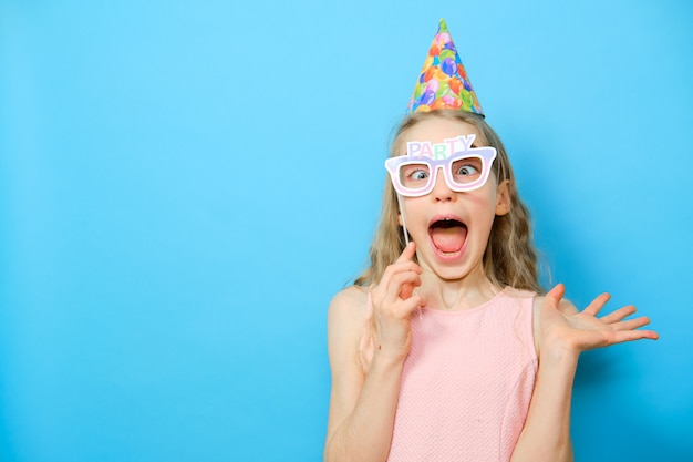 Blonde cheerful girl in funny glasses with the word party. happy birthday