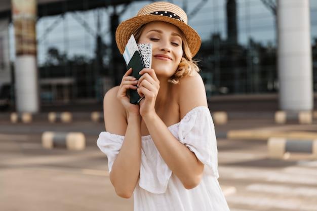 La donna bionda allegra in barcaiolo e vestito bianco tiene il passaporto e sorride sinceramente