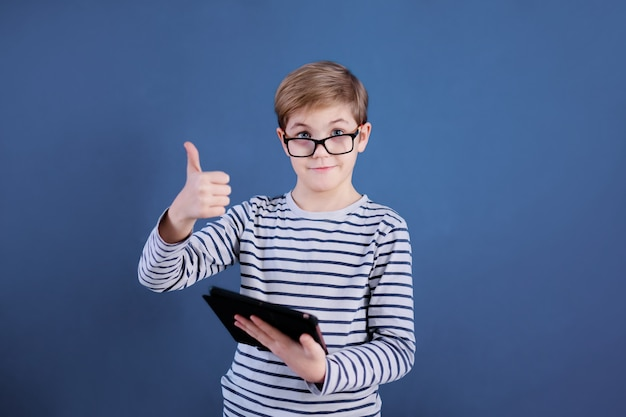 Blonde child boy with big glasses playing with tablet  on blue wall. education concept.