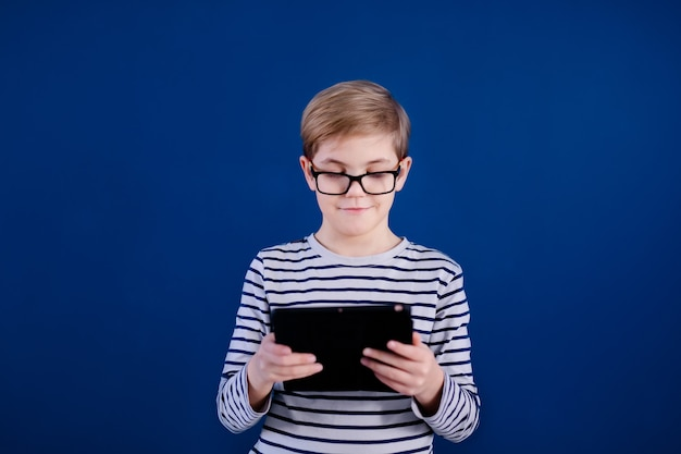 Blonde child boy with big glasses playing with tablet pc on blue wall. education concept.